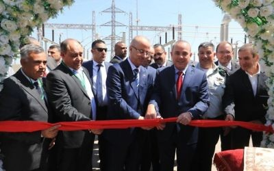 Israel's National Infrastructure Minister Yuval Steinitz (wearing red tie) and Palestinian Authority Prime Minister Rami Hamdallah cut the ribbon to mark the first ever commercial agreement between the Israeli and Palestinian energy companies to increase provision in the West Bank area of Jenin, July 10, 2017. Yoav Mordechai, Coordinator of Government Activities in the Territories, stands behind Steinitz,  with Yiftach Ron Tal, Israel Electric Corporation head, on the far right.(Yossi Weiss).