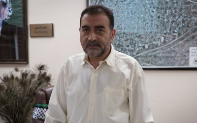 Mayor of Qalqiliya Hashim al-Masri stands in his office. (Luke Tress / Times of Israel)