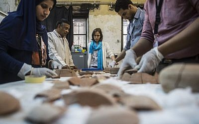 French Anita Quiles, a researcher in the French Institute of Eastern Archaeology (IFAO) in Cairo, stands near local staff at a dating laboratory inside the institute on May 14, 2017. (AFP PHOTO / KHALED DESOUKI)