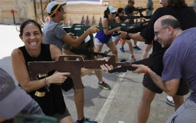 Foreign tourists train with a wooden gun as they participate in a two hour anti-terror course at the Caliber 3 shooting range, near the West Bank settlement of Efrat on July 18, 2017. (AFP PHOTO / MENAHEM KAHANA)