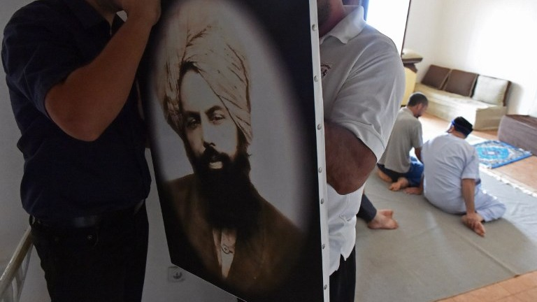 Members of Algeria's small Ahmadi community put up a photo of Mirza Ghulam Ahmad, the founder of the Ahmadiyya movement, at a house in Tilpasi, west of Algiers, on June 30, 2017. (AFP Photo/Ryad Kramdi)