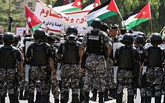 Jordanian security forces stand on guard as protesters wave Jordanian flags and chant slogans during a demonstration near the Israeli embassy in the capital Amman on July 28, 2017. (AFP Photo/Khalil Mazraawi)