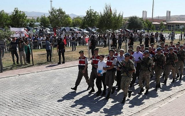 Turkish paramilitary officers escort defendants, among them Kemal Batmaz (first row, C) and Akin Ozturk (second row, C),  as they arrive for their trial at Sincan Penal Institution at the 4th Heavy Penal Court near Ankara on August 1, 2017.  (AFP Photo/Adem Altan)