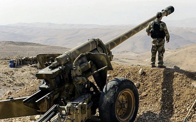 A tour guided by the Lebanese Shiite Hezbollah terror group shows one of the group's fighters standing next to an artillery gun in a mountainous area around the Syrian town of Flita near the border with Lebanon, August 2, 2017.  (AFP PHOTO / LOUAI BESHARA)