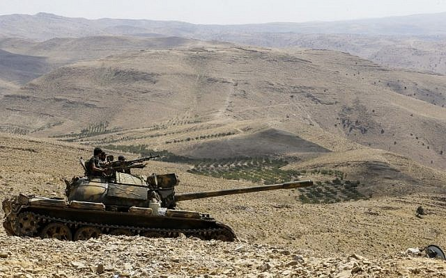 A picture taken on August 2, 2017 during a tour guided by the Lebanese Shiite Hezbollah group shows members of the Syrian government forces riding over a tank at a position in a mountainous area around the Syrian town of Flita near the border with Lebanon. (AFP/LOUAI BESHARA)