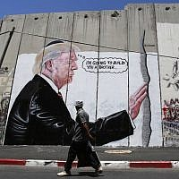 A Palestinian man walks past a graffiti depicting US President Donald Trump on the Israeli security barrier in the West Bank town of Bethlehem on August 4, 2017. (AFP/Musa Al Shaer)