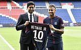 Brazilian superstar Neymar (R) poses with his jersey next to Paris Saint Germain's (PSG) Qatari president Nasser Al-Khelaifi during his official presentation at Paris' Parc des Princes stadium on August 4, 2017. (AFP Photo/Philippe Lopez)