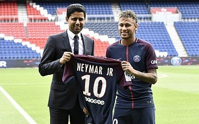 Brazilian superstar Neymar (R) poses with his jersey next to Paris Saint Germain's (PSG) Qatari president Nasser Al-Khelaifi during his official presentation at Paris' Parc des Princes stadium on August 4, 2017. (AFP Photo/Philippe Lopez)