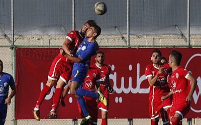 A player from Gaza's Shabab Rafah soccer team (blue) jumps to head the ball against a member of Hebron's Ahly Al-Ahli team during the second leg of the Palestinian Cup final at the stadium in the city of Dura, near the West Bank town of Hebron, on August 4, 2017. (AFP Photo/Hazem Bader)