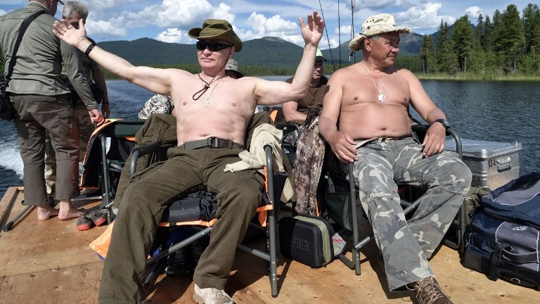 Russian President Vladimir Putin (L), accompanied by Defense Minister Sergei Shoigu, gestures as he fishes in the remote Tuva region in southern Siberia. The picture was taken between August 1 and 3, 2017. (AFP Photo/Sputnik/Alexey Nikolsky)