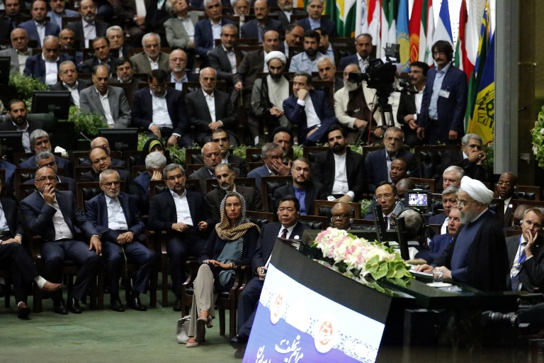 EU foreign policy chief Federica Mogherini (C) listens as Iran's President Hassan Rouhani (R) delivers a speech after being sworn in before parliament in Tehran, on August 5, 2017. (AFP PHOTO / ATTA KENARE)