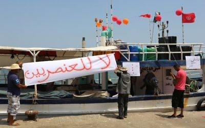 Tunisian fishermen hang banners as they gather on August 6, 2017 in the port of Zarzis in southeastern Tunisia to protest against a possible berthing of the C-Star vessel, hired by far-right activists from a group which calls itself 'Generation Identity' to prevent would-be migrants from reaching Europe. The writing in Arabic reads: 'No to Racism' (AFP PHOTO / FATHI NASRI)