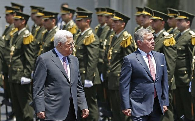 Jordan's King Abdullah II and Palestinian Authority President Mahmoud Abbas observe the honor guard during a visit in the West Bank city of Ramallah on August 7, 2017. (AFP PHOTO / ABBAS MOMANI)