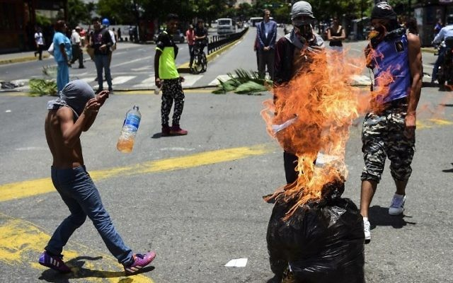 Anti-government activists demonstrate against Venezuelan President Nicolas Maduro at a barricade set up on a road in Caracas on August 8, 2017. (AFP PHOTO / Ronaldo SCHEMIDT)