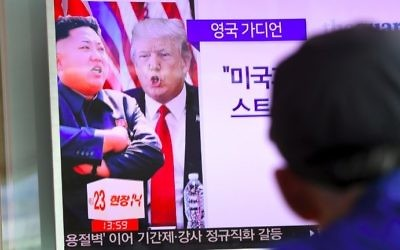 A man watches a news program at a railway station in Seoul showing US President Donald Trump (C) and North Korean leader Kim Jong-Un (L) on August 9, 2017. (AFP Photo/Jung Yeon-Je)