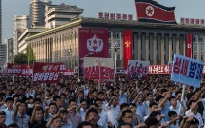 People wave banners and shout slogans as they attend a rally in support of North Korea's stance against the US, on Kim Il-Sung square in Pyongyang on August 9, 2017. (AFP PHOTO / KIM Won-Jin)