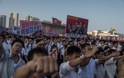 People wave banners and shout slogans as they attend a rally in support of North Korea's stance against the US, on Kim Il-Sung square in Pyongyang on August 9, 2017. (AFP/KIM Won-Jin)
