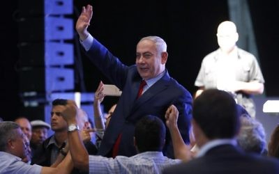 Prime Minister Benjamin Netanyahu waves to the crowd as he's surrounded by Likud party members and activists during a mass show of support at a gathering in the Tel Aviv Convention Center, August 9, 2017. (AFP/Jack Guez)