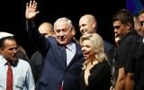 Prime Minister Benjamin Netanyahu, center, and his wife Sara, center-right, react during a gathering by Likud party members and activists to show support for them as they face corruption investigations, held at the Tel Aviv Convention Center, August 9, 2017. (AFP/Jack GUEZ)