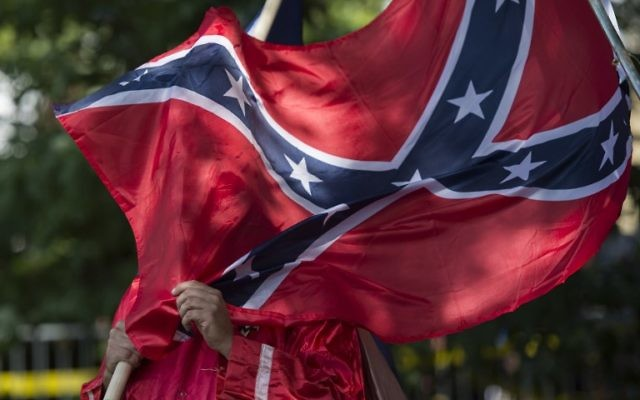 This file photo taken on July 8, 2017 shows a member of the Ku Klux Klan holding a Confederate flag over his face during a rally, calling for the protection of Southern Confederate monuments, in Charlottesville, Virginia. (AFP PHOTO / ANDREW CABALLERO-REYNOLDS)