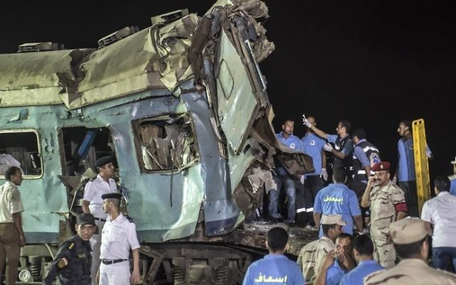 Egyptian officials and emergency personnel remove the wreckage of a collision between two trains on August 11, 2017 near Khorshid station in Alexandria. (AFP PHOTO / KHALED DESOUKI)