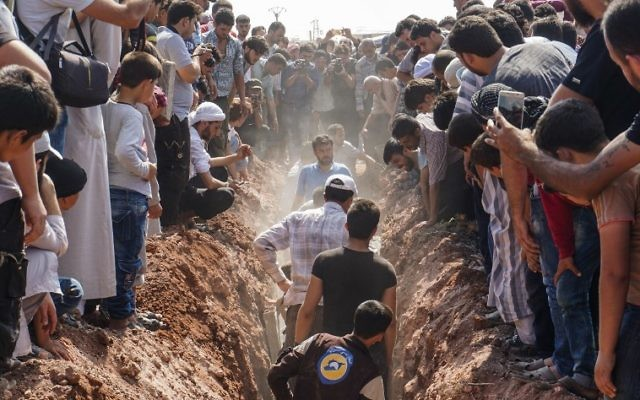 Members of the Syrian civil defense volunteers, also known as the White Helmets, bury their fellow comrades during a funeral in Sarmin, a jihadist-held town 9 kilometers east of Syria's northwestern city of Idlib on August 12, 2017, after seven were shot dead early in the morning. (AFP/Omar Haj Kadour)