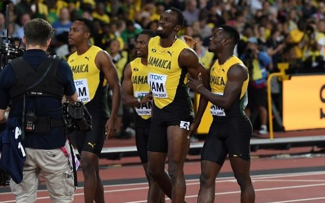 Jamaica's Julian Forte (L), Yohan Blake (2L) and Omar McLeod (R) console Jamaica's Usain Bolt (2R) after Bolt pulled up injured in the final of the men's 4x100m relay athletics event at the 2017 IAAF World Championships at the London Stadium in London on August 12, 2017. (AFP Photo/Kirill Kudryavtsev)