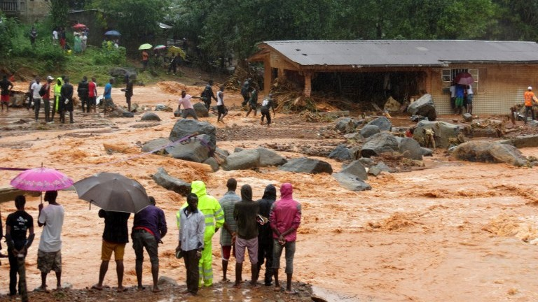 People look on as floodwaters rage past a damaged building in an area of Freetown on August 14, 2017, after landslides struck the capital of the west African state of Sierra Leone. (AFP Photo/Saidu Bah)