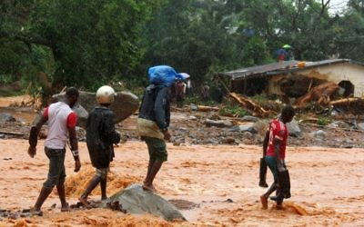Residents walk through floodwaters past a damaged building in an area of Freetown on August 14, 2017, after landslides struck the capital of the west African state of Sierra Leone. (AFP PHOTO / SAIDU BAH)