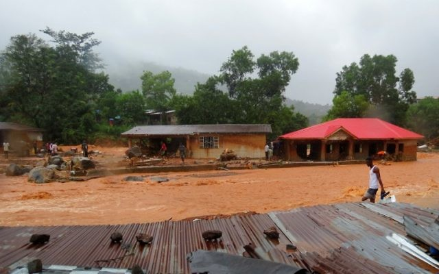 A resident walks through floodwaters past a damaged building in an area of Freetown on August 14, 2017, after landslides struck the capital of the west African state of Sierra Leone.                At least 312 people were killed and more than 2,000 left homeless when heavy flooding hit Sierra Leone's capital of Freetown, leaving morgues overflowing and residents desperately searching for loved ones. An AFP journalist at the scene saw bodies being carried away and houses submerged in two areas of the city, where roads turned into churning rivers of mud and corpses were washed up on the streets.  / AFP PHOTO / SAIDU BAH