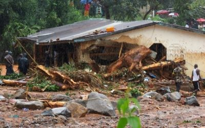 Bystanders and rescue personnel gather beside a flood damaged building in an area of Freetown on August 14, 2017, after landslides struck the capital of the west African state of Sierra Leone. (AFP PHOTO / SAIDU BAH)
