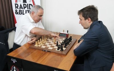 Grandmaster chess player Garry Kasparov, left, makes the first move as he plays grandmaster Sergey Karjakin of Russia in the opening round of the Grand Chess Tour at the Chess Club and Scholastic Center in St. Louis, August 14, 2017.  (AFP/BILL GREENBLATT)