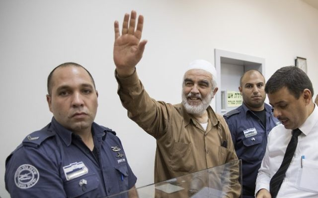 Sheikh Raed Salah, center, smiles as he arrives at the Israeli Rishon Lezion Magistrate's Court on August 15, 2017. (AFP/JACK GUEZ)