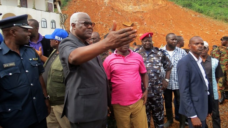 Sierra Leone president Ernest Bai Koroma (2nd-L) visits the site of a mudslide near Freetown on August 15, 2017, after landslides struck the capital of the west African state. (AFP Photo/Saidu Bah)