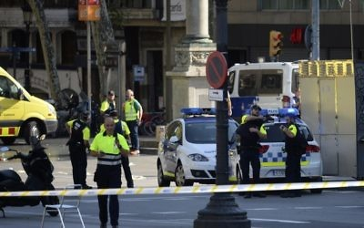 Medical staff and policemen stand in a cordoned-off area after a van plowed into the crowd, injuring several people, in Barcelona on August 17, 2017. (AFP/Josep Lago)