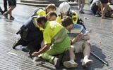A person is helped by Spanish policemen and two men after a van ploughed into the crowd, killing at least 13 people and injuring around 100 others, on the Las Ramblas Boulevard in Barcelona, Spain, on August 17, 2017. (AFP/Nicolas Carvalho Ochoa)