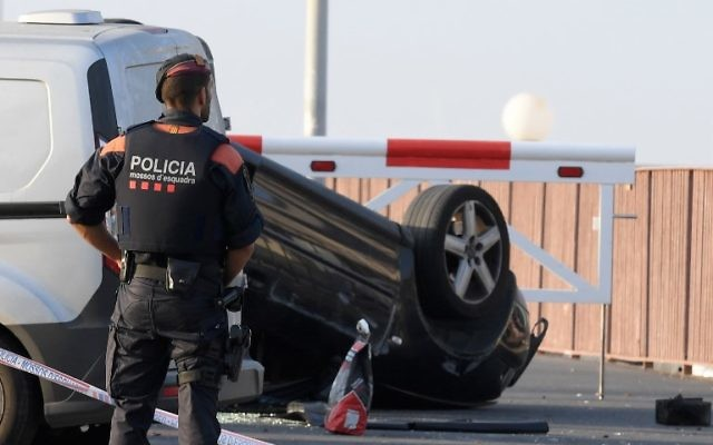 A policeman stands by a car involved in a terrorist attack in Cambrils, a city 120 kilometers south of Barcelona, on August 18, 2017. (AFP/LLUIS GENE)