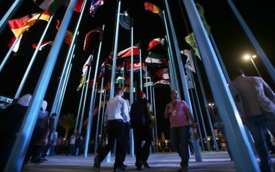 Participants and visitors walk past flags of various countries during the opening of the Damascus International Fair late on August 17, 2017, in the Syrian capital. (AFP/Youssef KARWASHAN)