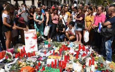 People stand next to flowers, candles and other items set up on the Las Ramblas boulevard in Barcelona as they pay tribute to the victims of the Barcelona attack on August 18, 2017. (AFP/PASCAL GUYOT)
