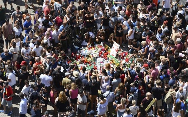 People gather to leave tributes on August 18, 2017 for the victims at the spot where a van ploughed into the crowd on August 17, 2017, killing 13 people and injuring over 100, on the Las Ramblas Boulevard in Barcelona, Spain. (AFP/Josep Lago)