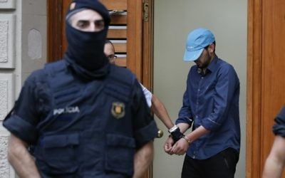 Catalan autonomous police officers, known as Mosso d'Esquadra, detain a cuffed suspect in Ripoll during a search linked to the deadly terror attacks in Barcelona and the seaside resort of Cambrils on August 18, 2017, a day after a van plowed into the crowd, killing 14 people and injuring over 100 on the Rambla in Barcelona.  (AFP PHOTO / PAU BARRENA)