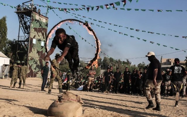 Young Palestinians jump though a ring of fire during a military graduation ceremony at a Hamas summer camp in Khan Yunis, in the southern Gaza Strip, on August 18, 2017. ( AFP PHOTO / SAID KHATIB)
