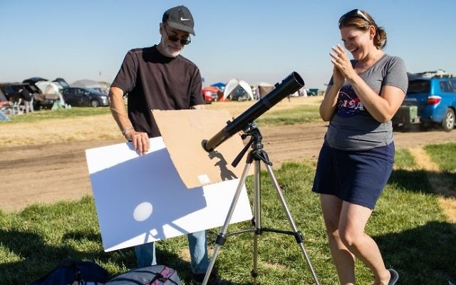 John Adlington and Tricia Dacie successfully setup a telescope to project an image of the Sun on a white matte board. They are some of the total solar eclipse enthusiasts gathering in Madras, Oregon, on August 18, 2017. (AFP PHOTO / ROB KERR)