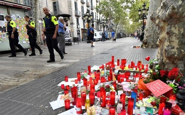 Police officers walk by tributes left for victims of the Barcelona attack, on the Las Ramblas boulevard in Barcelona on August 19, 2017, two days after a van ploughed into the crowd, killing 13 persons and injuring over 100. (AFP PHOTO / Pascal GUYOT)