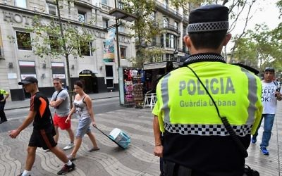 Police officers stand guard on the Las Ramblas boulevard in Barcelona on August 19, 2017, two days after a van ploughed into the crowd, killing 13 persons and injuring over 100. (AFP PHOTO / Pascal GUYOT)