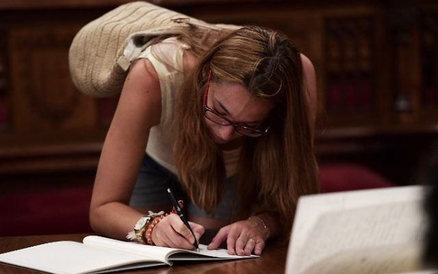 A woman writes a message on a book of condolences at the Salo de Cent of the town hall of Barcelona on August 19, 2017, two days after a van ploughed into the crowd, killing 13 persons and injuring over 100 (AFP PHOTO / JAVIER SORIANO)