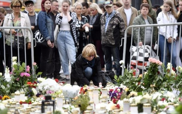 Candles and flowers are left at the makeshift memorial by well wishers for the victims of Friday's stabbings at the Turku Market Square, Finland on August 19, 2017. (AFP Photo/Lehtikuva/Vesa Moilanen)