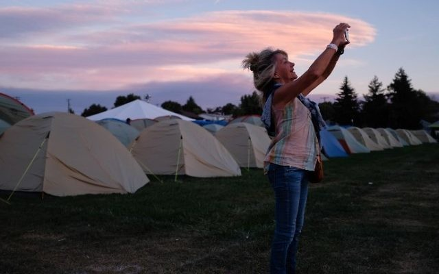 Suzanne Rapley of Santa Barbara, California takes a photo at sunset with her iPhone August 18, 2017,she is one of many total solar eclipse enthusiasts gathering in Madras, Oregon and staying in organized campgrounds, the rural central and eastern part of Oregon is hosting dozens of festivals to help manage the crowds a million visitors are expected to the region for the Monday August 21, 2017. (AFP PHOTO / ROB KERR)