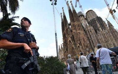 A police officer stands by the Sagrada Familia basilica in Barcelona on August 20, 2017, before a mass to commemorate victims of two devastating terror attacks in Barcelona and Cambrils. (AFP PHOTO / PASCAL GUYOT)