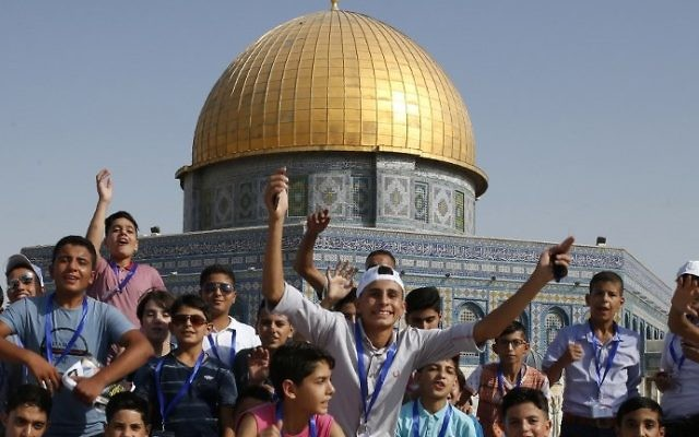 Palestinian children from the Gaza Strip pose for a picture near the Dome of the Rock mosque in the Al-Aqsa mosque compound in Jerusalem's old city on August 20, 2017 as they visit the city for the first time as part of an exchange program run by the UN agency for Palestinian refugees. (AFP PHOTO / AHMAD GHARABLI)